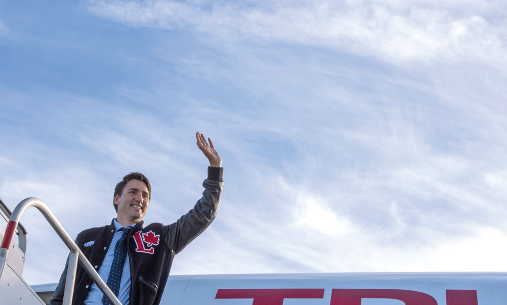 Liberal Leader Justin Trudeau waves as he boards his plane en route to Calgary, Sunday, October 18, 2015 in Edmonton. THE CANADIAN PRESS/Paul Chiasson