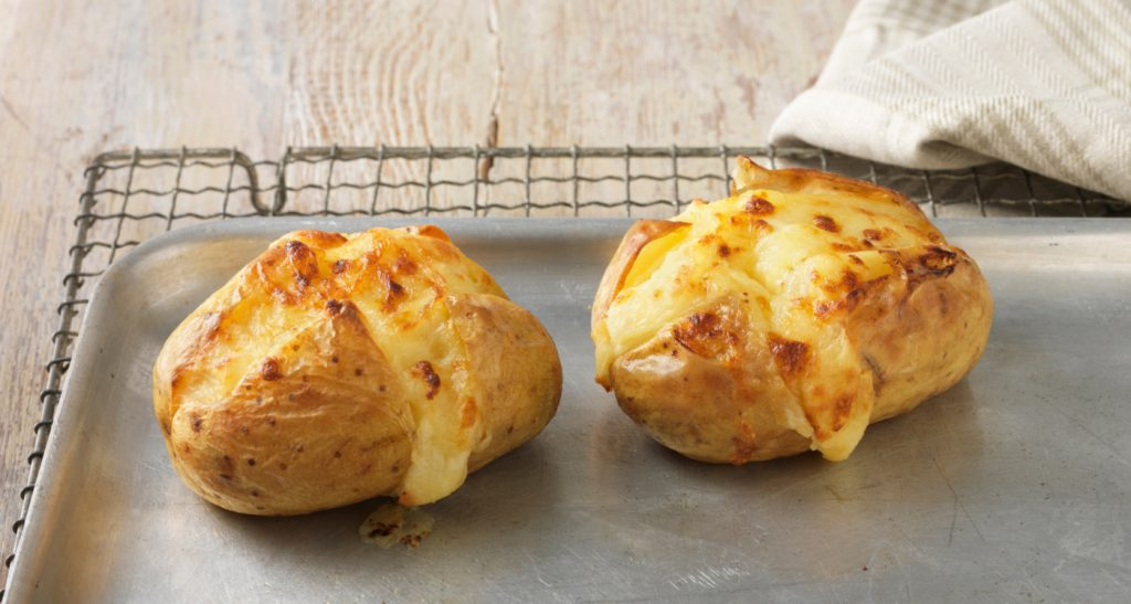 Baked potatoes with cheese on metal baking sheet