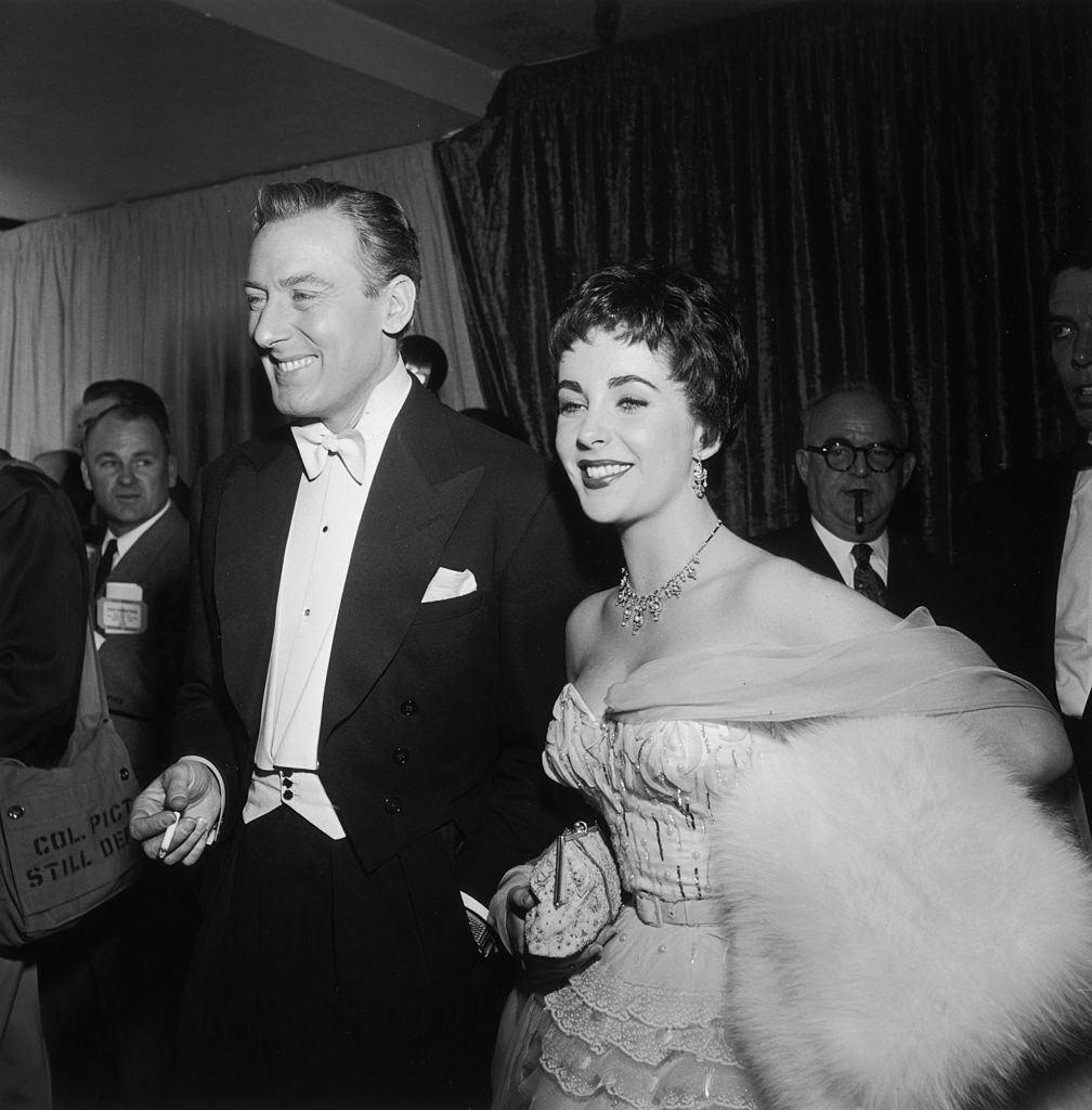 25th March 1954: British-born actor Elizabeth Taylor smiles while walking with her second husband, British actor Michael Wilding (1912-1979), at the Academy Awards, Los Angeles, California. Taylor holds a white fur stole under her arm. Wilding smokes a cigarette. (Photo by Hulton Archive/Getty Images)
