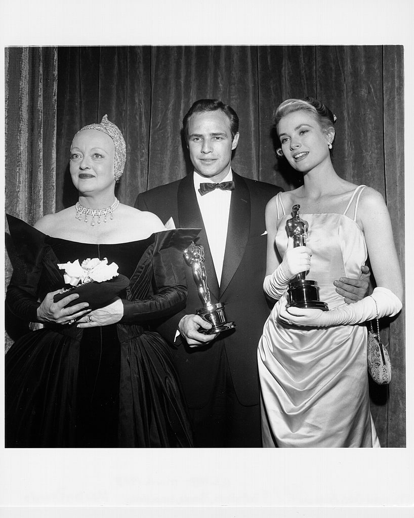 "NEW YORK - MARCH 30: Actress and presenter for the best actor award at the 27th Academy Awards Bette Davis poses for a portrait with best actor winner for his performance in the movie ""On The Waterfront"" Marlon Brando, and best actress winner for her performance in ""The Country Girl"" backstage at the Academy Awards which were held on March 30, 1955 in New York City, New York. (Photo by Michael Ochs Archives/Getty Images)"