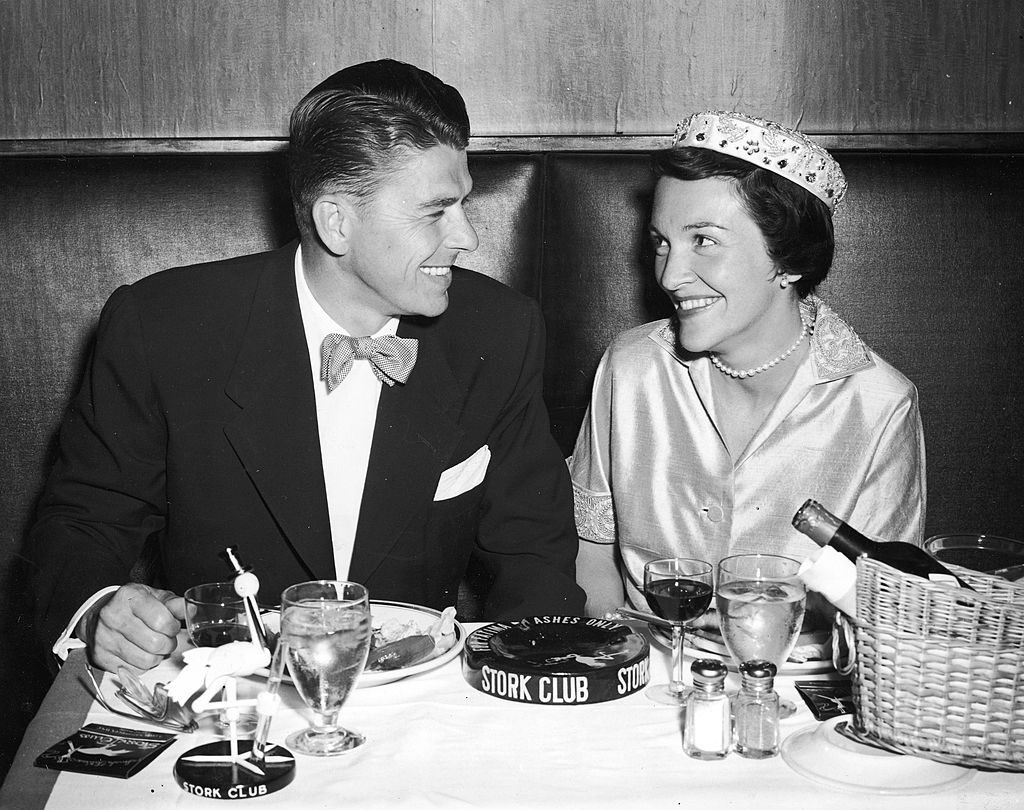 American actor Ronald Reagan and his wife Nancy Reagan smile as they have their honeymoon dinner at the Stork Club, New York City, 1952. (Photo by Hulton Archive/Getty Images)
