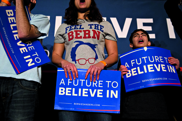 Attendees hold campaign signs and cheer during a campaign rally for Senator Bernie Sanders, an independent from Vermont and 2016 Democratic presidential candidate, at Danceland Ballroom in Davenport, Iowa, U.S., on Friday, Jan. 29, 2016. Sanders is counting on young voters turning out to win next Mondays Iowa caucuses. But by putting an emphasis on his plans for Social Security, the Vermont Senator isnt ceding older Democrats to Hillary Clinton. Photographer: Andrew Harrer/Bloomberg via Getty Images