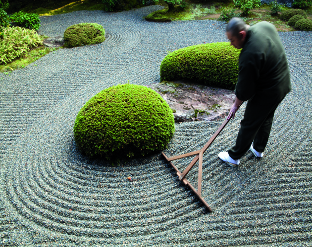 KYOTO, JAPAN - 2010/11/20: Rev Takafumi Kawakami is the vice-abbot at Shunkoin Temple and teaches classes about Zen culture and meditation and serves as a bridge between the Eastern and Western cultures. Here Rev Takafumi is raking the temple's Zen Garden. The Garden of Bolders, or Sazareishi-no-niwa, is the main garden of Shunkoin. The theme of the garden is the Great Shrine of Ise in Mie Prefecture. The Great Shrine of Ise is the head shrine of all Shinto shrines in Japan. This garden houses a shrine to Toyouke-no-omikami, a goddess of agriculture.. (Photo by John S. Lander/LightRocket via Getty Images)