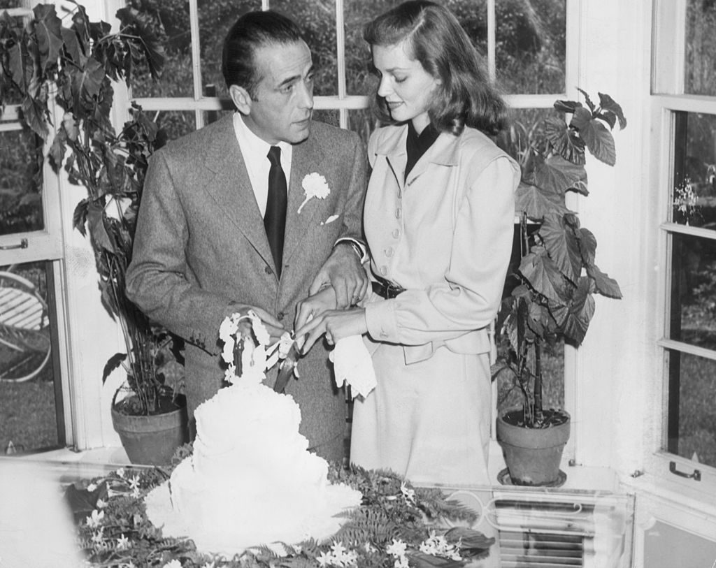 21st May 1945: Married American actors Lauren Bacall and Humphrey Bogart (1899 - 1957) cut the cake at their wedding. (Photo by Hulton Archive/Getty Images)