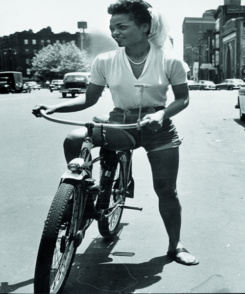 Singer Eartha Kitt riding her bicycle down the street. (Photo by Gordon Parks/The LIFE Picture Collection/Getty Images)
