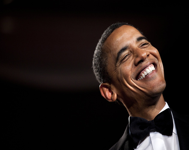 Obama smiling from ear to ear on a black background.