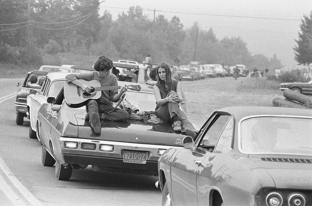 A couple play the guitar sitting on their car on the way to the Woodstock Festival, August 1969. (Photo by Baron Wolman/Iconic Images/Getty Images)