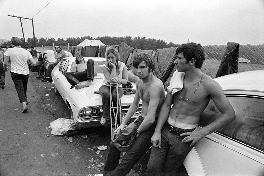 A group of visitors lean on the cars to rest at the Woodstock Music & Art Fair celebrated in Bethel, NY, August 15, 1969. (Photo by Baron Wolman/Iconic Images/Getty Images)