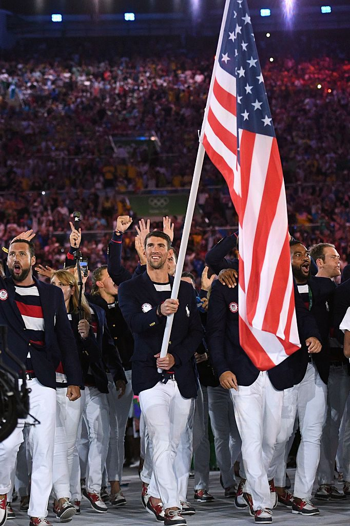 TOPSHOT - The USA's Michael Phelps carries the flag during the opening ceremony of the Rio 2016 Olympic Games at the Maracana stadium in Rio de Janeiro on August 5, 2016. / AFP / Leon NEAL (Photo credit should read LEON NEAL/AFP/Getty Images)