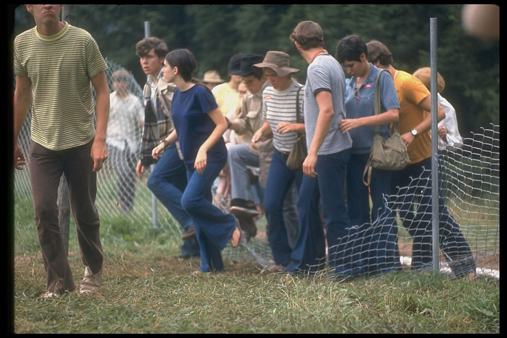 View of a group of people as they step over a torn-down fence in order to enter the grounds of the Woodstock Music & Art Festival, Bethel, New York, August 1969. (Photo by Bill Eppridge/The LIFE Picture Collection/Getty Images)