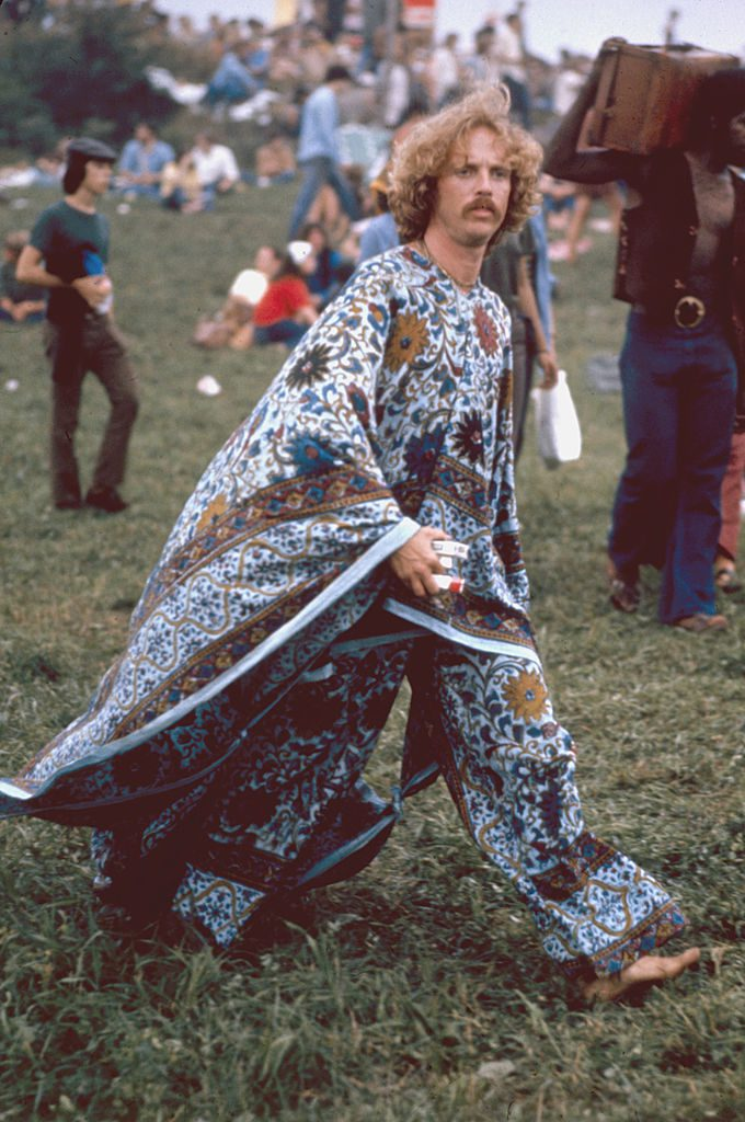 An unidentified, mustachioed young man, barefoot but dressed in a flowered kaftan, carries what appears to be three packs of cigarettes as he strides through the grass at the Woodstock Music and Arts Fair in Bethel, New York, August 15 - 17 (and part of the 18th), 1969. (Photo by Bill Eppridge/The LIFE Picture Collection/Getty Images)