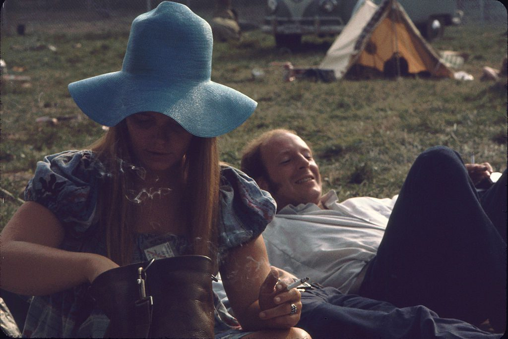 View of an unidentified pair of festival goers on the grass on the grounds of the Woodstock Music and Arts Fair, Bethel, New York, August 1969. The man lies on his back, while the woman, a wide-brimmed floppy hat oh her head and her festival ticket around her neck, smokes and looks through her purse. The festival ran from August 15 to 18. (Photo by Ralph Ackerman/Getty Images)