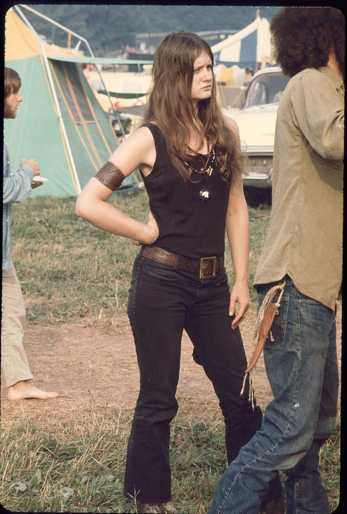 Young woman member of the White Panthers, a group formed to support the work of the Black Panthers stands aside as young man sets up a tent at the Woodstock music festival, August 1969. (Photo by Ralph Ackerman/Getty Images)