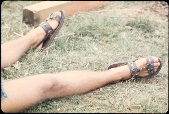 A man wearing sandals laying in the field at the Woodstock music festival, August 1969. (Photo by Ralph Ackerman/Getty Images)