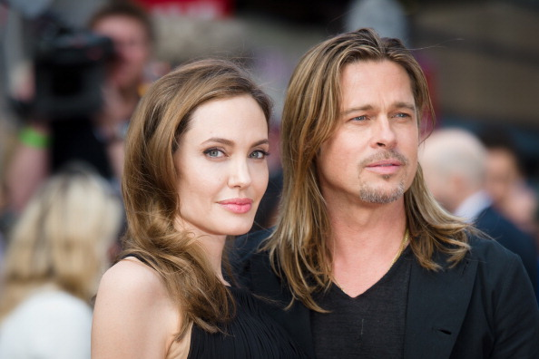 """US actress and humanitarian campaigner Angelina Jolie (L) poses with her US actor and fiance Brad Pitt as she arrives for the UK premiere of Brad Pitt's latest film """"World War Z"""" in Leicester Square in central London on June 2, 2013. Jolie, 37, revealed in an article in the May 14 edition of The New York Times that she chose to undergo surgery to minimize the risk she might develop breast cancer due to the inheritance of a """"faulty gene."""" The actress's partner and fellow screen star Brad Pitt led worldwide praise, declaring Jolie heroic, followed by her doctors, other stars and thousands of supporters, who took to social media to praise her openness. AFP PHOTO / LEON NEAL (Photo credit should read LEON NEAL/AFP/Getty Images)"""