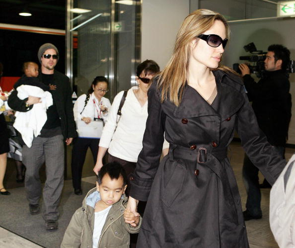 """NARITA, JAPAN: Hollywood stars Angelina Jolie (R) and Brad Pitt (L), accompanied by Jolie's children, arrive at Narita Airport in suburban Tokyo, 27 November 2005. The two stars are now here for the promotion of their movie """"Mr. and Mrs. Smith"""", which will be screened in Japan from 03 December. AFP PHOTO / Yoshikazu TSUNO (Photo credit should read YOSHIKAZU TSUNO/AFP/Getty Images)"""