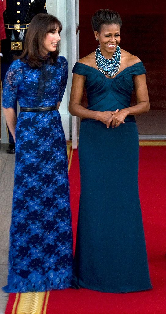 """WASHINGTON, DC - MARCH 14: Samantha Cameron, wife of British Prime Minister David Cameron, and United States first lady Michelle Obama pose for photos on the North Portico of the White House for a """"state dinner,"""" in Washington, D.C., on Wednesday, March 14, 2012. (Photo by Nikki Kahn/The Washington Post via Getty Images)"""