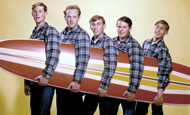 """LOS ANGELES - AUGUST 1962: Rock and roll band """"The Beach Boys"""" pose for a portrait with a surfboard in August 1962 in Los Angeles, California. (L-R) Brian Wilson, Mike Love, Dennis Wilson, Carl Wilson, David Marks. This image was used on the cover of 'Surfin' USA'. (Photo by Michael Ochs Archives/Getty Images)"""