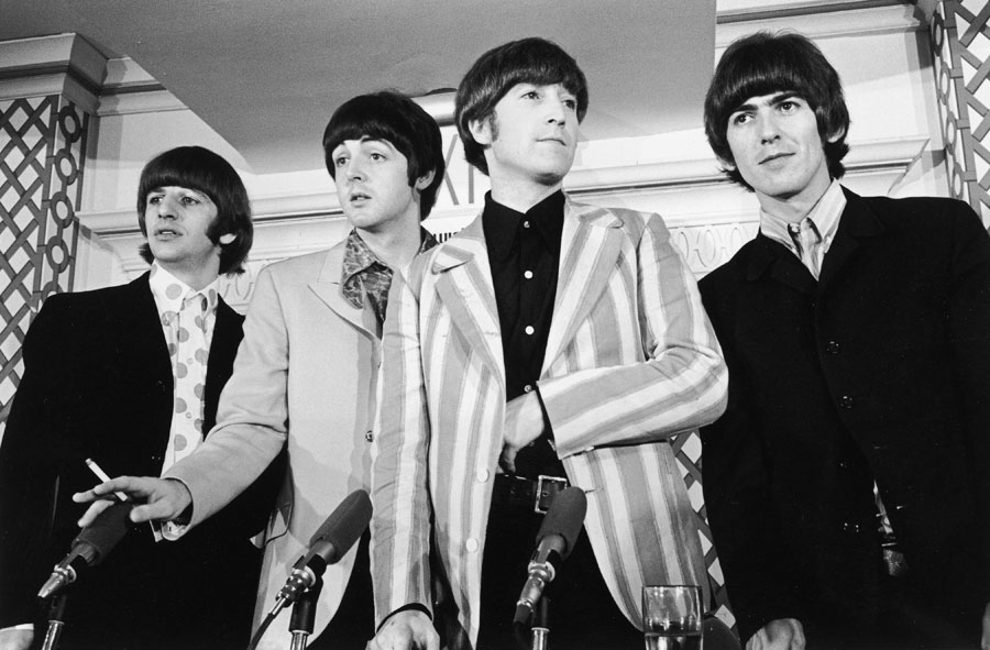 British pop group the Beatles standing in front of four microphones at a press conference where they discussed their concert at Shea Stadium, New York City. L-R: Ringo Starr, Paul McCartney, John Lennon (1940 -1980), and George Harrison (1943 - 2001).