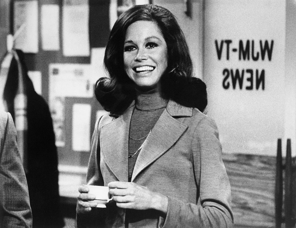 (Original Caption) Still from The Mary Tyler Moore Show showing Moore standing, smiling, inside of the WJM newsroom. Moore is shown from the waist-up, holding a cup of coffee.