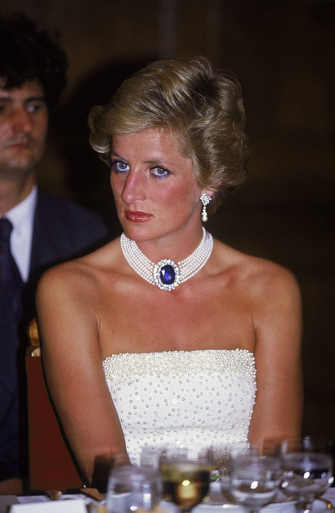 The Princess of Wales (1961 - 1997) wears a white Catherine Walker dress embroidered with pearls to a formal dinner in Budapest, 7th May 1990. She accessorises it with a pearl and sapphire choker. (Photo by Jayne Fincher/Princess Diana Archive/Getty Images)