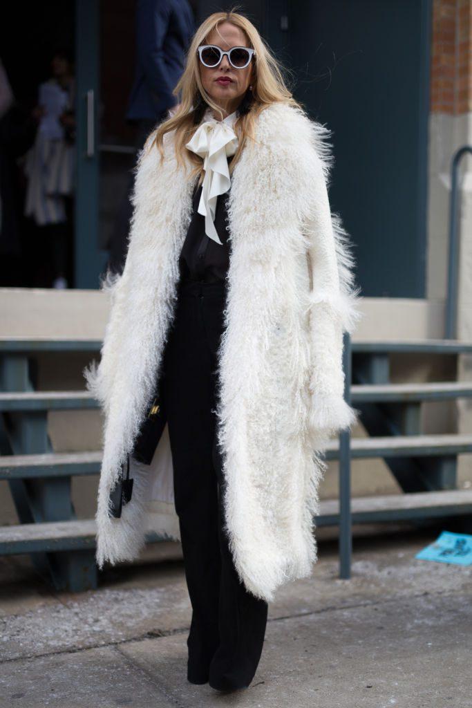 Woman wearing a white coat over black pants suit.