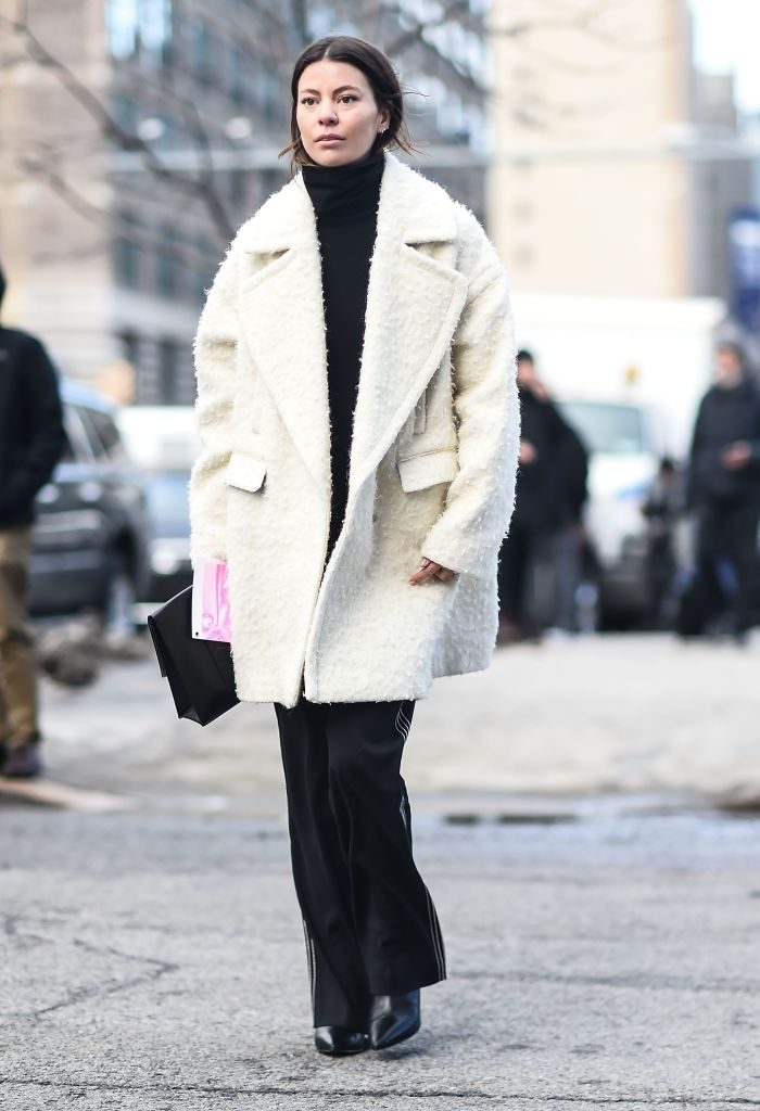 Woman wearing short white coat over black pants and top.