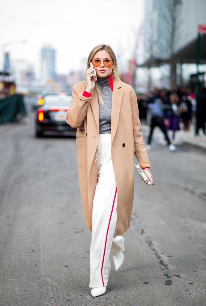 Woman wearing white pants and long camel coat.
