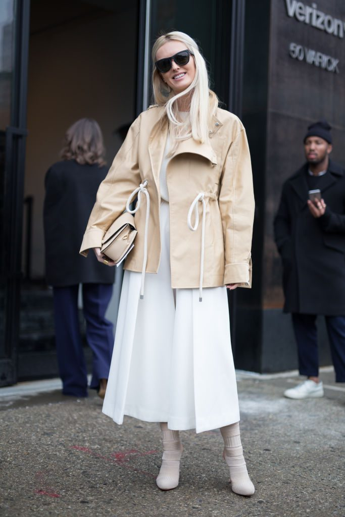 Woman wearing white skirt with a beige jacket.