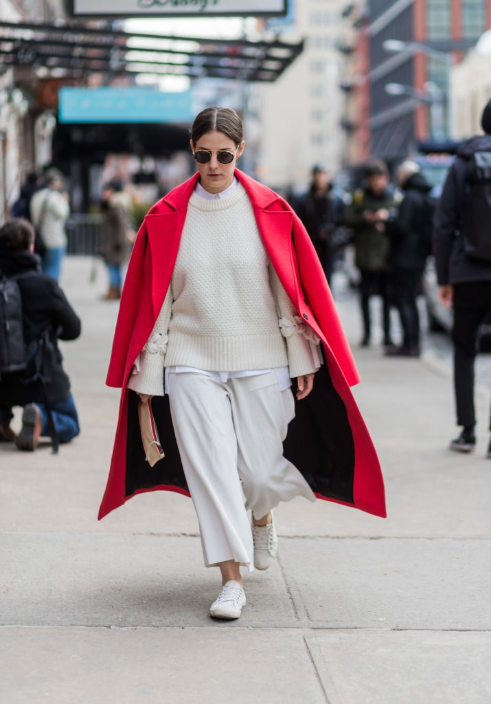 Photo of woman wearing white sweater and pants with a long red coat.