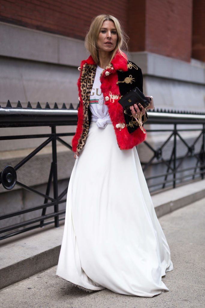 Woman wearing long white skirt and t-shirt with a red jacket.