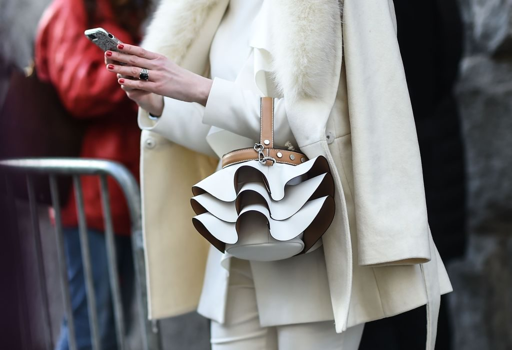 Woman wearing a white coat and white suit, carrying a white handbag.