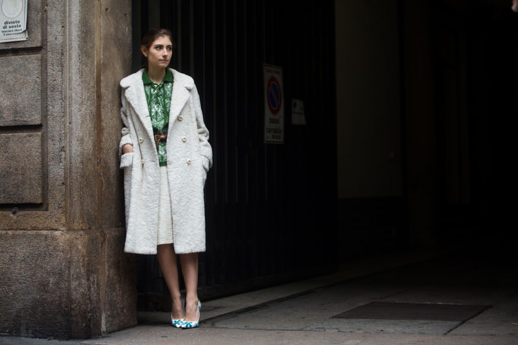 Woman wearing green shirt with white skirt and coat.