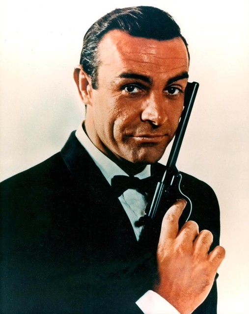 Sean Connery as James Bond holds up a pistol.