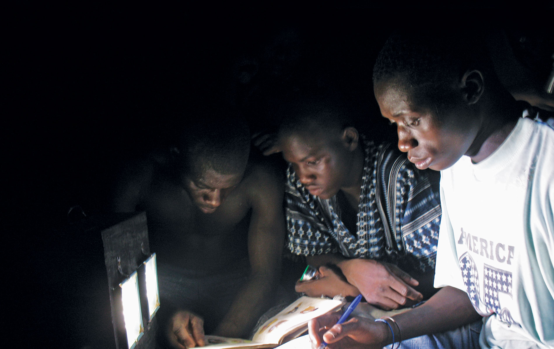 Three children huddled around the light provided by a low-cost LED lamp.