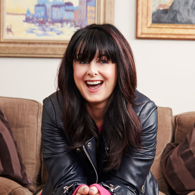 Author Marian Keyes sitting on a couch, smiling with her hands folded, wearing a leather jacket