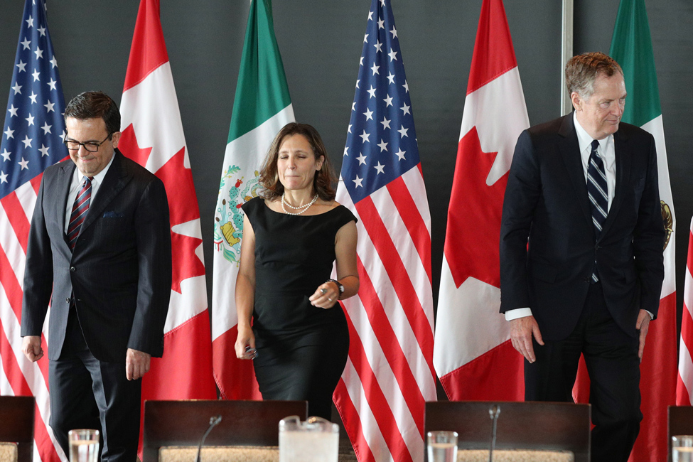 Trade representatives from the U.S., Canada and Mexico meet to discuss NAFTA. Each representative walks toward camera with flags of each country in background.