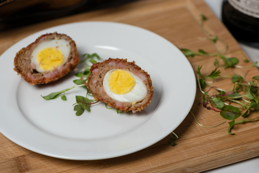Two scotch eggs on a white plate.