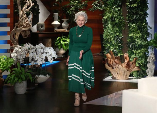 Helen Mirren makes her entrance on the Ellen DeGeneres show wearing a green dress and gold necklace.