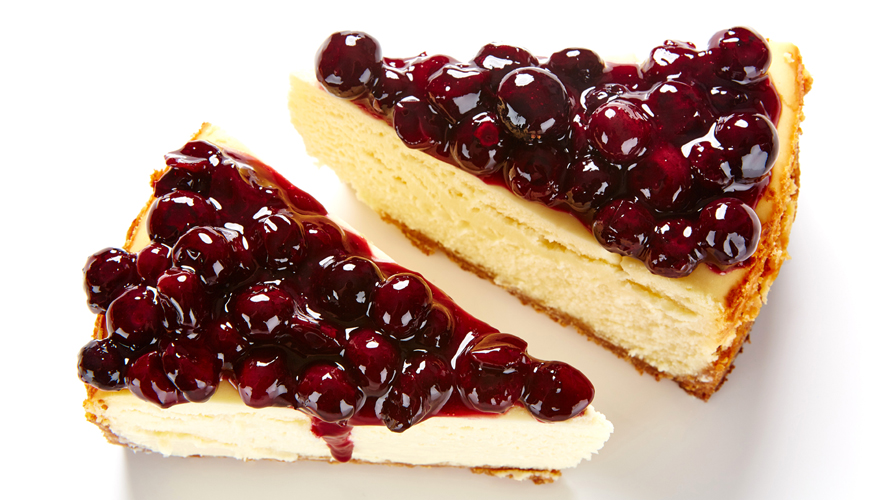 A piece of blueberry cheesecake with a buttery and golden graham cracker crust topped with a silky, scrumptious cheesecake filling and a sweet blueberry sauce.
