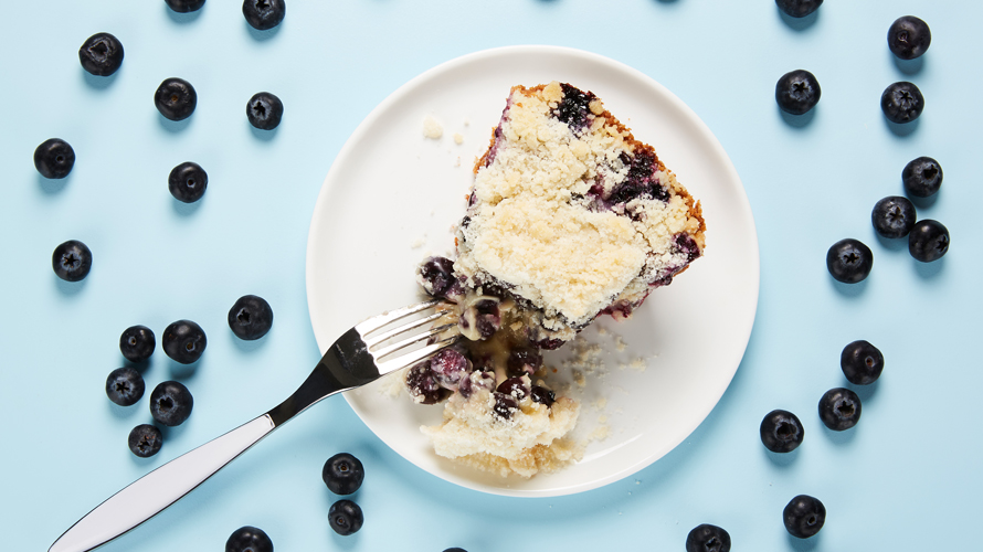 Creamy blueberry pie with sweet streusel topping served on a white plate surrounded by blueberries.