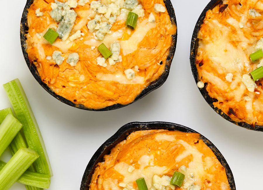 Lightened up buffalo chicken dip consisting of reduced fat cream cheese, greek yogurt, Red Hot Buffalo Wing Sauce and shredded chicken breast served in small black bowls.