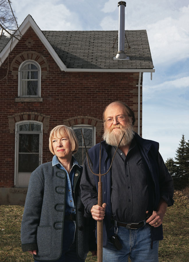 Organic farming couple posing in front of their farmhouse. The husband is holding a pitch fork, sporting a large grey beard while the wife is sporting a short blonde haircut.
