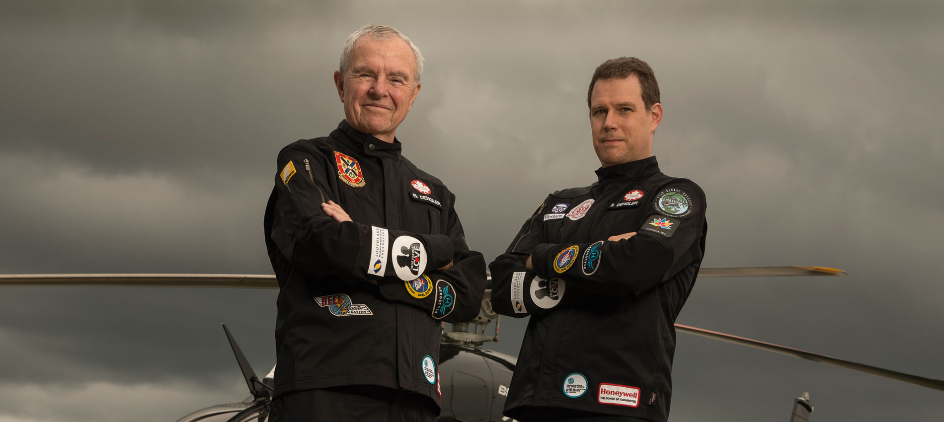 Father and son, Steven and Bob Dengler pose in front of their helicopter with their arms crossed, wearing black pilot uniforms.