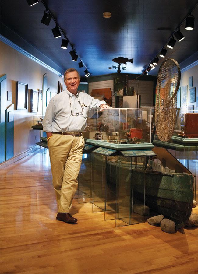 A smiling Hoagy Carmichael Jr. leans against a glass case inside the Cascapedia River Museum.