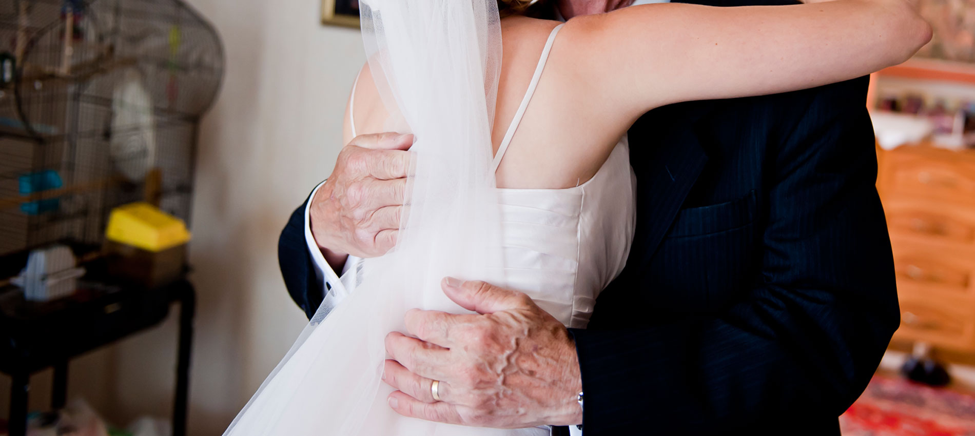 A father hugs his daughter on her wedding day.