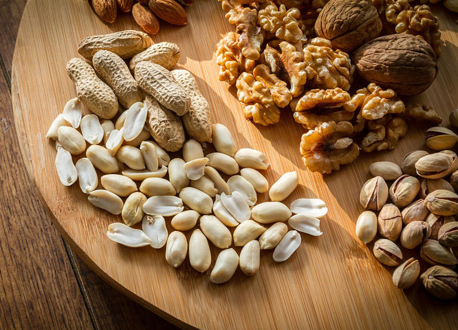 An assortment of nuts on a wooden cutting board.