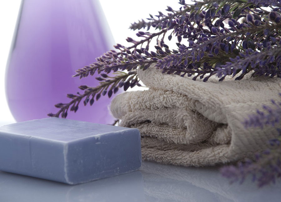 Lavender soap beside a white towel covered in lavender.