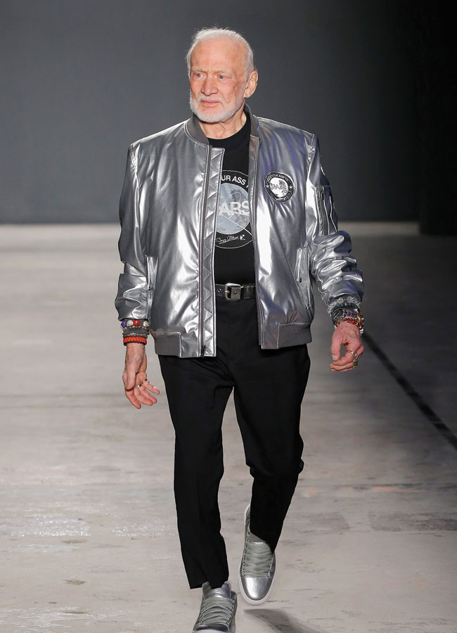 A silver haired and bearded Buzz Aldrin sports a metallic silver lettermen's jacket and silver sneakers during New York Fashion Week.