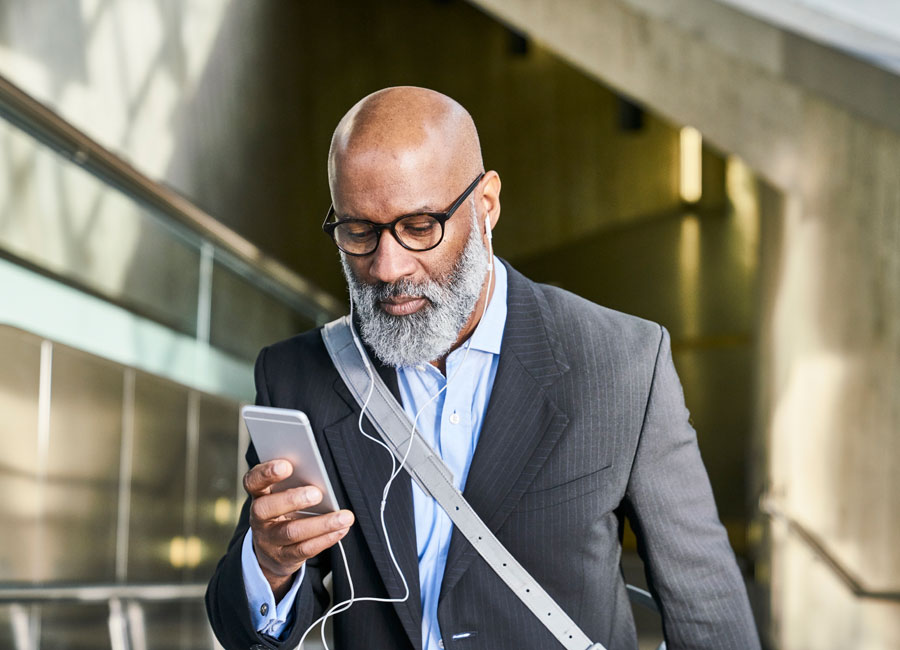 A bald man with a white beard and glasses glances down as his smart phone as he walks indoors.
